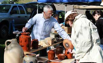 Brimfield Antique Market - Michael McCue from Black Angus Antiques in Pennsylvania set up with stoneware, redware, butter prints, penny dolls, and other folk art items at the opening of May's Antique Market Thursday at 9:00am. Michael seemed happy with the pace of selling.