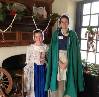Two Colonial Gems, John Chads House and the Barns-Brinton House - Colonial girls standing in front of the Christmas decorated fireplace, 2013.