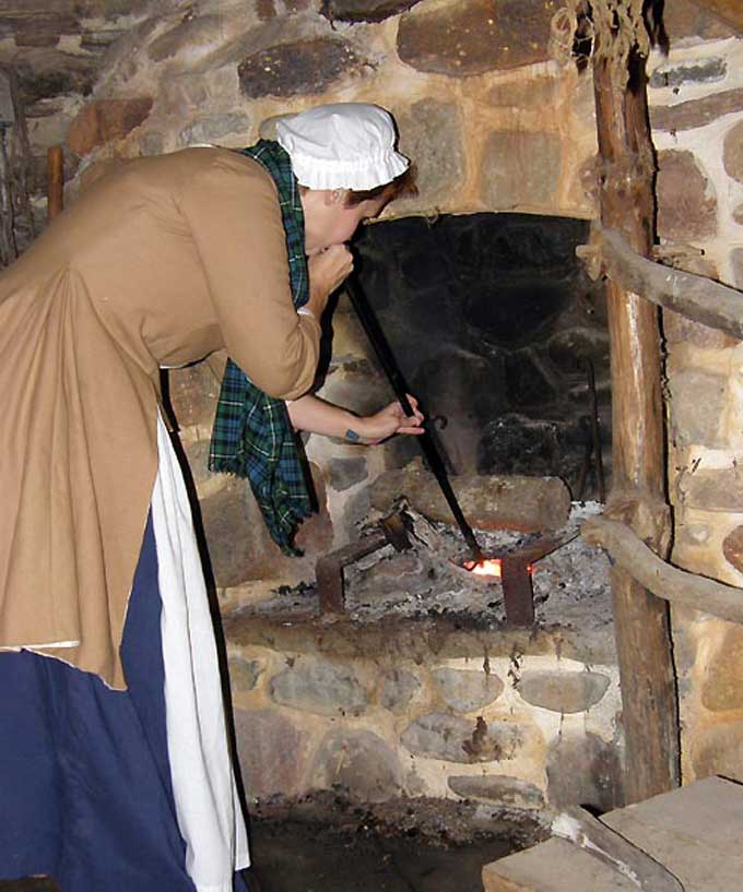 Salem, NJ Yuletide Tour - A lady keeping the fire going in the log cabin at Johan Printz Memorial Park