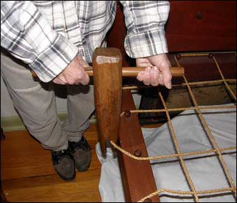 Bed Roping - An antique bed key is used to tighten the rope. In this photo, the bed key will be turned counterclockwise to tighten the second rope below the headboard.